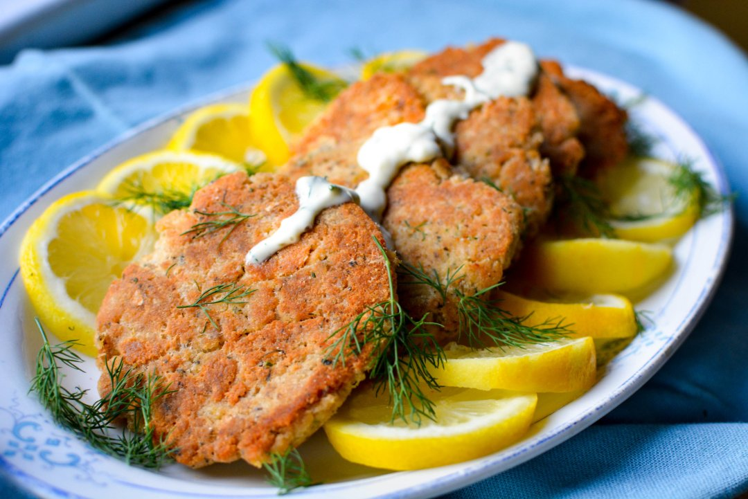 salmon cakes with lemon dill mayo on plate with slices of lemons