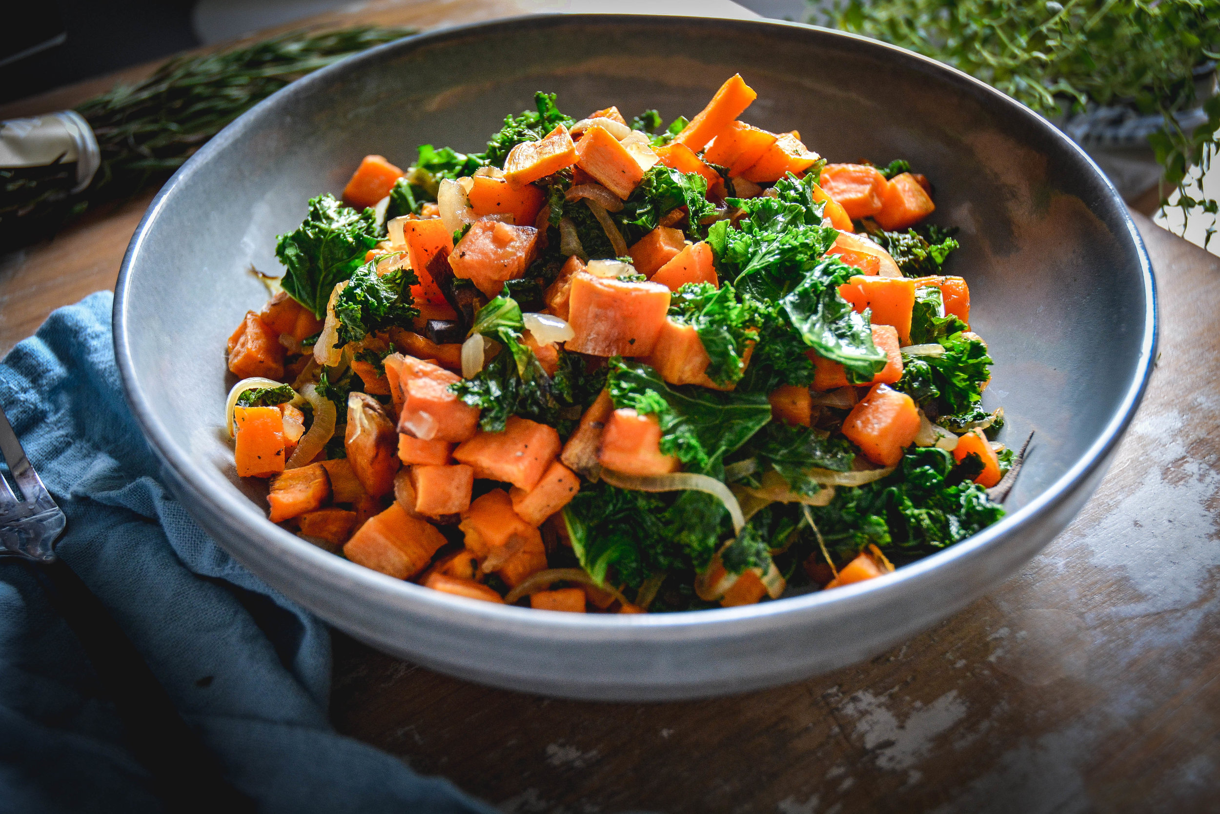 sweet potatoes with kale in bowl, on table with blue napkin
