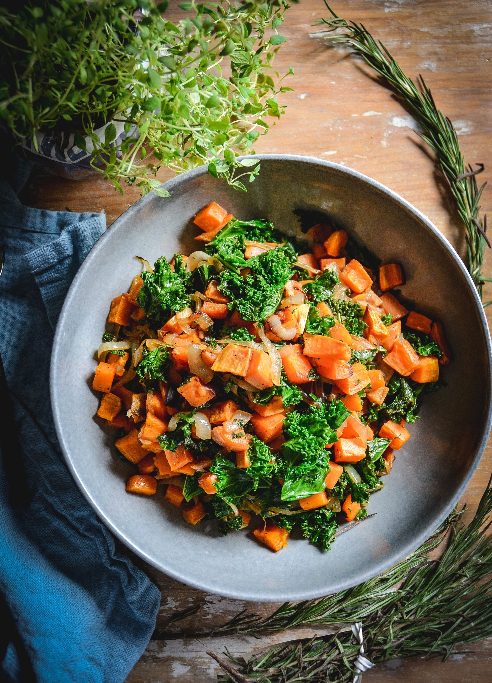 sweet potatoes with kale in large bowl on table with thyme and rosemary