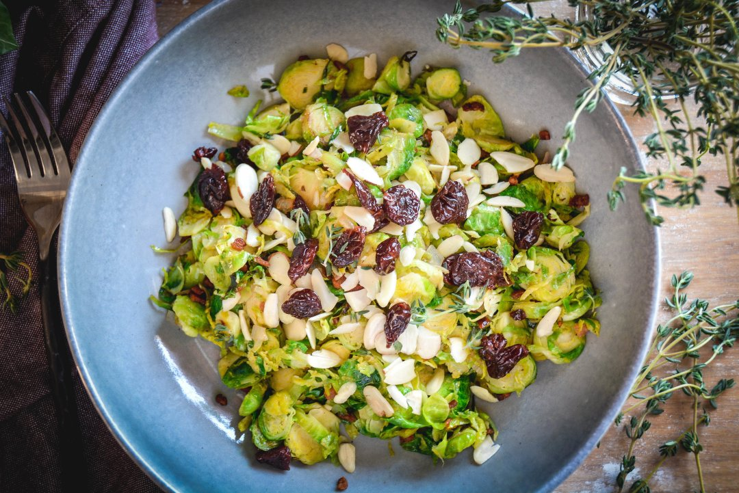 brussels sprouts salad with bacon and dried cherries in grey bowl with fork and thyme
