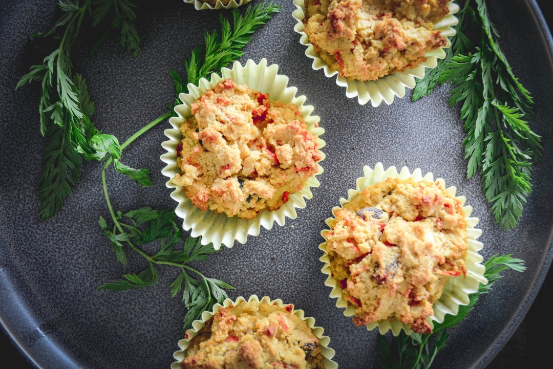 Paleo Cardamom Carrot Muffins on plate with greens