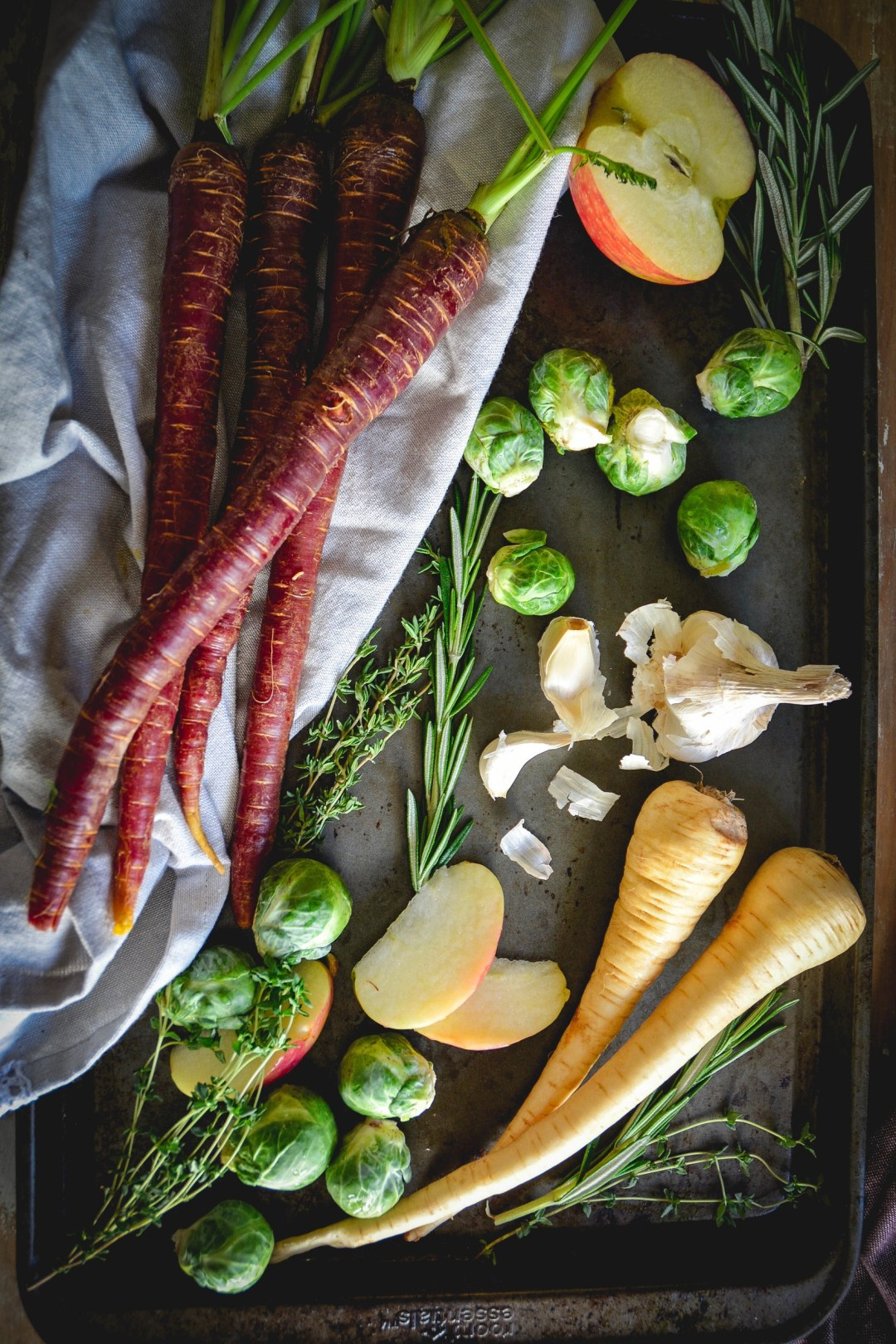 carrots, brussels sprouts, apple, parsnip on tray with herbs and napkin