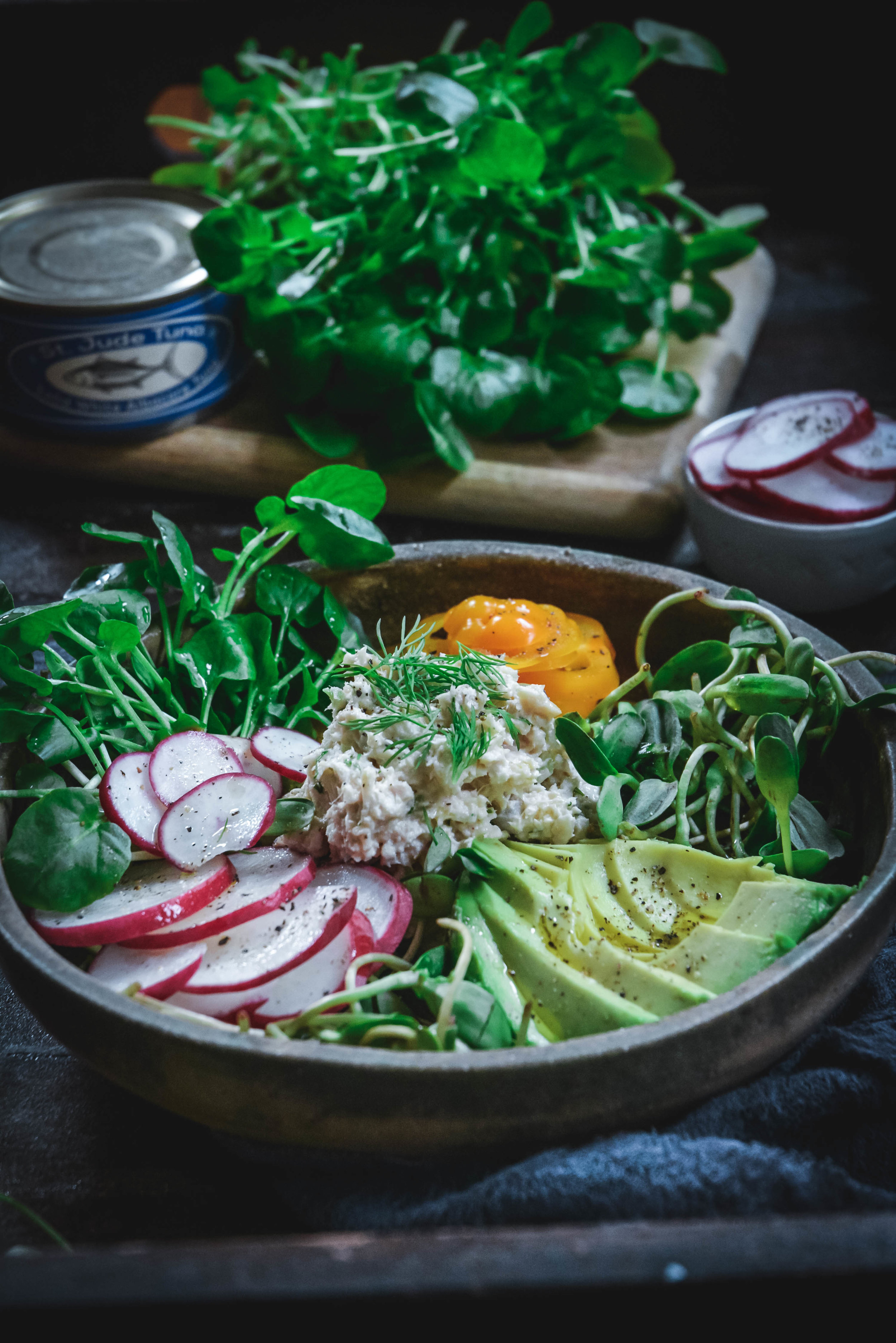 Tuna salad on plate with avocado, orange pepper, greens and sliced radishes and a can of St. Jude Tuna