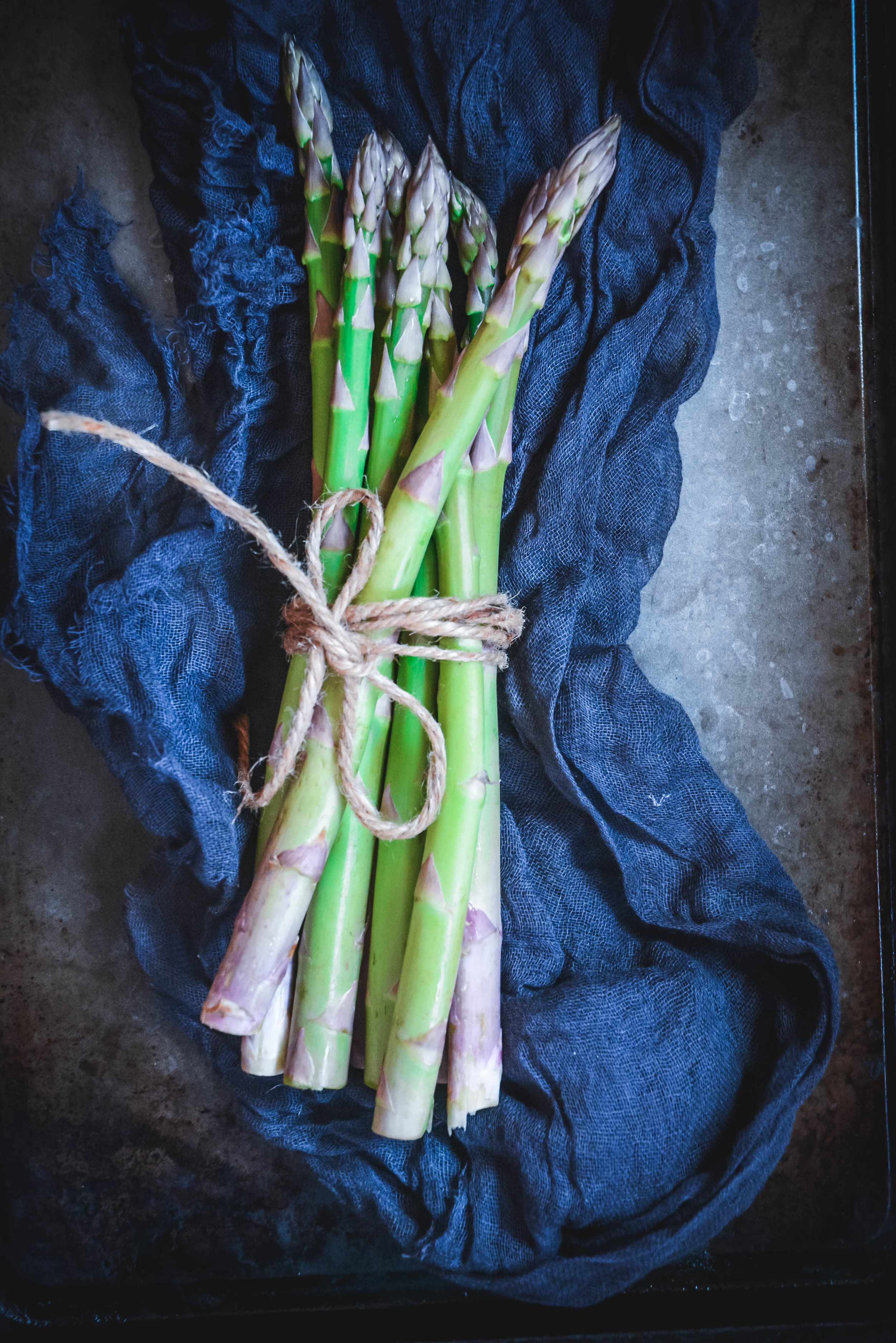 Asparagus on blue napkin tied with string