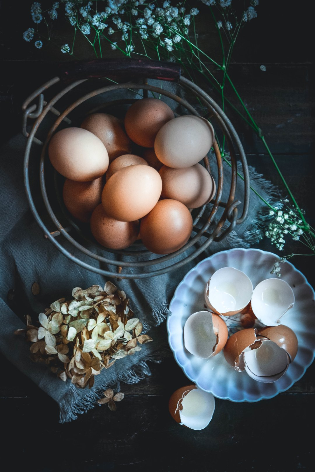 eggs in basket, egg shells on plate, dried hydrangea, baby's breath flowers