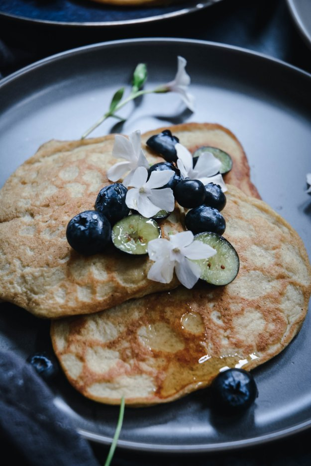 pancakes on plate topped with blueberries and periwinkle flowers