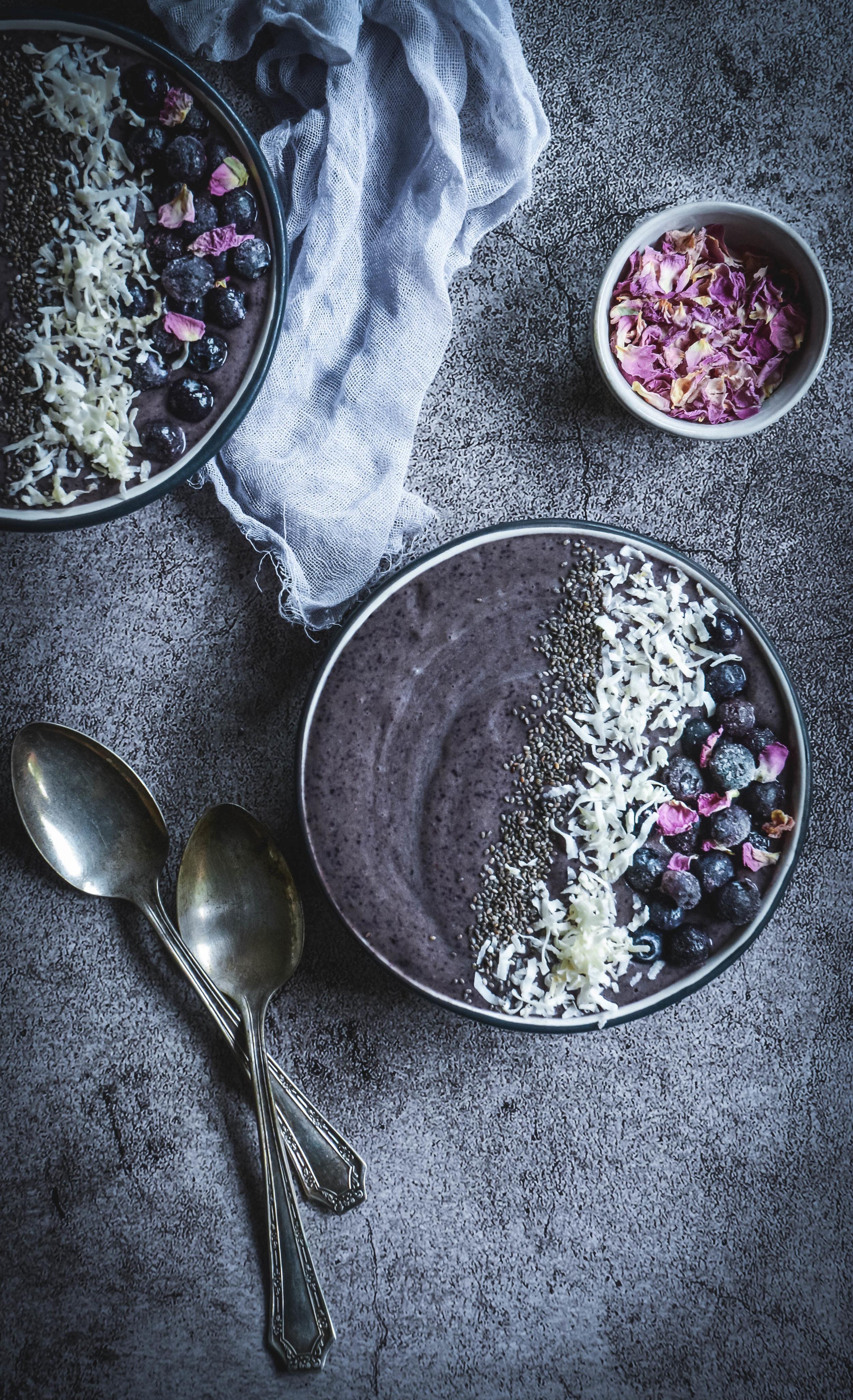 Smoothie bowls, napkin, two spoons, rose petal bowl