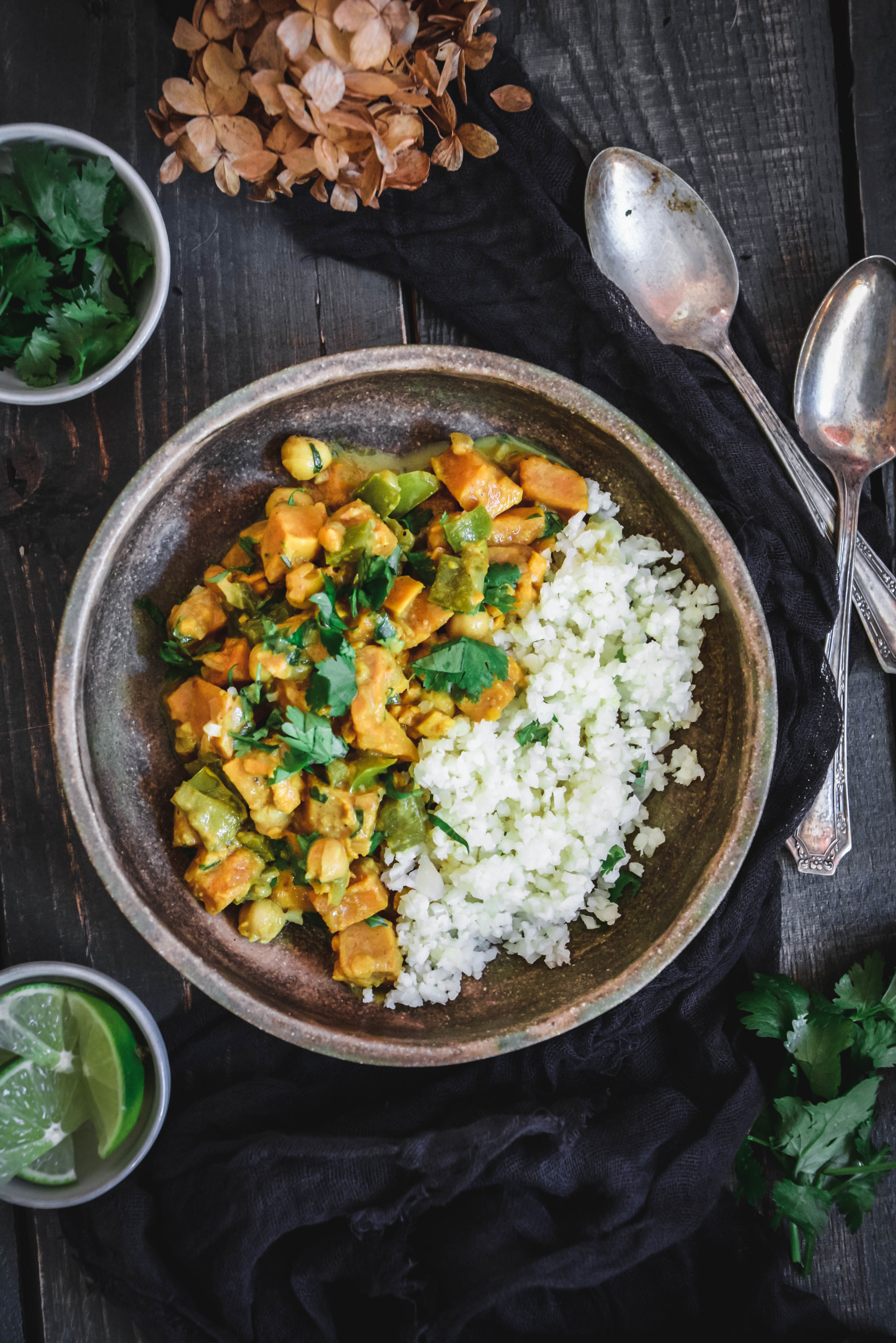 Coconut chickpea curry with sweet potatoes and cauliflower rice, in bowl with spoons napkin, herbs and lime