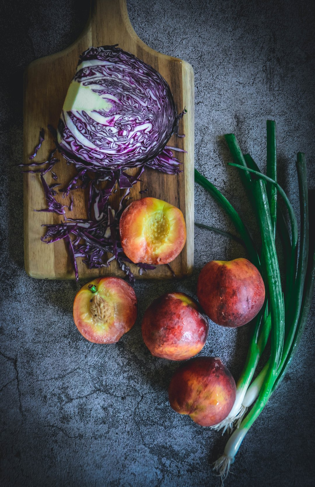Peaches, red cabbage and scallions on cutting board