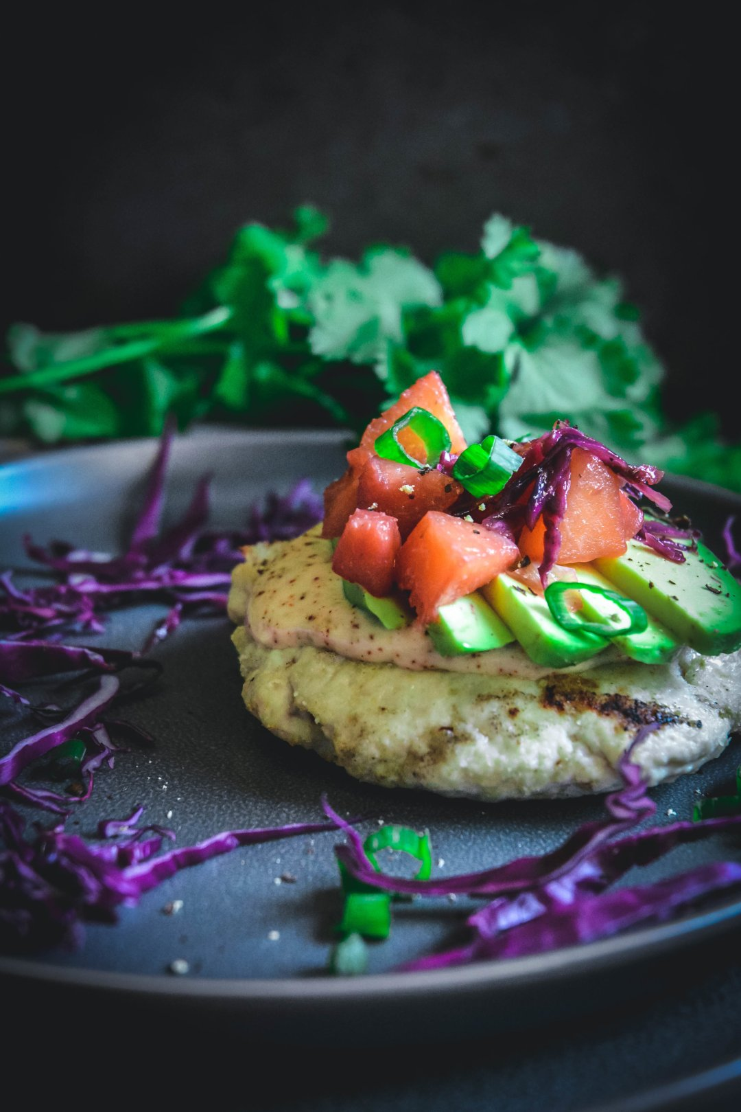 Turkey burgers on plate with avocado, peach chutney and cilantro