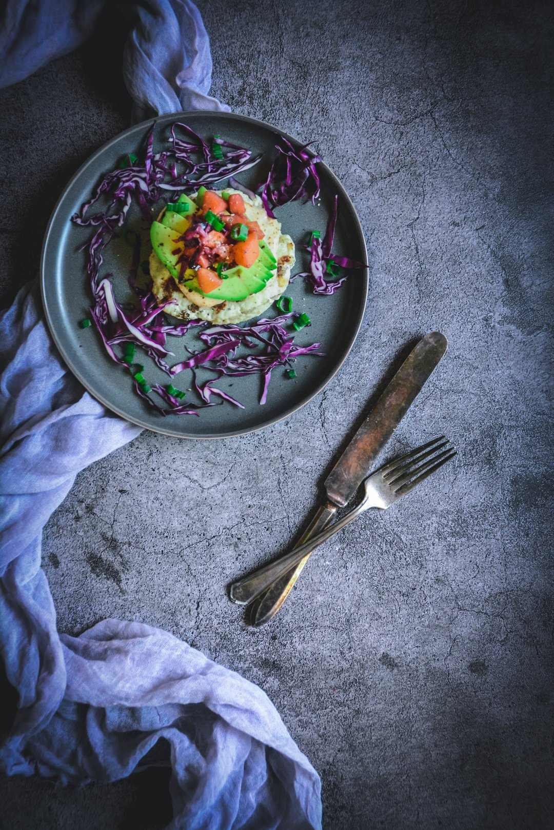 Turkey burger with peach chutney, on plate with napkin and fork and knife