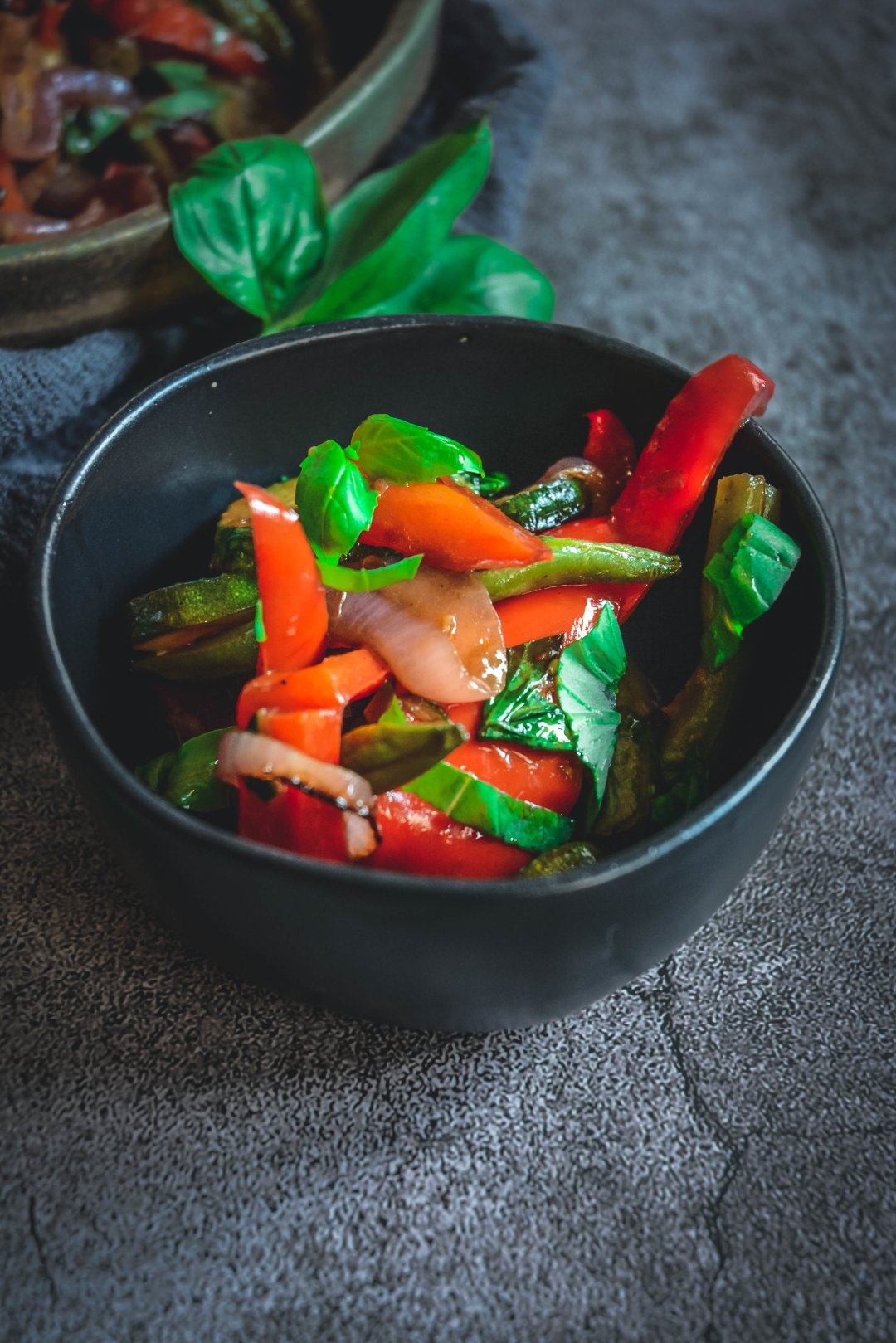 Grilled vegetables in small bowl with fresh basil