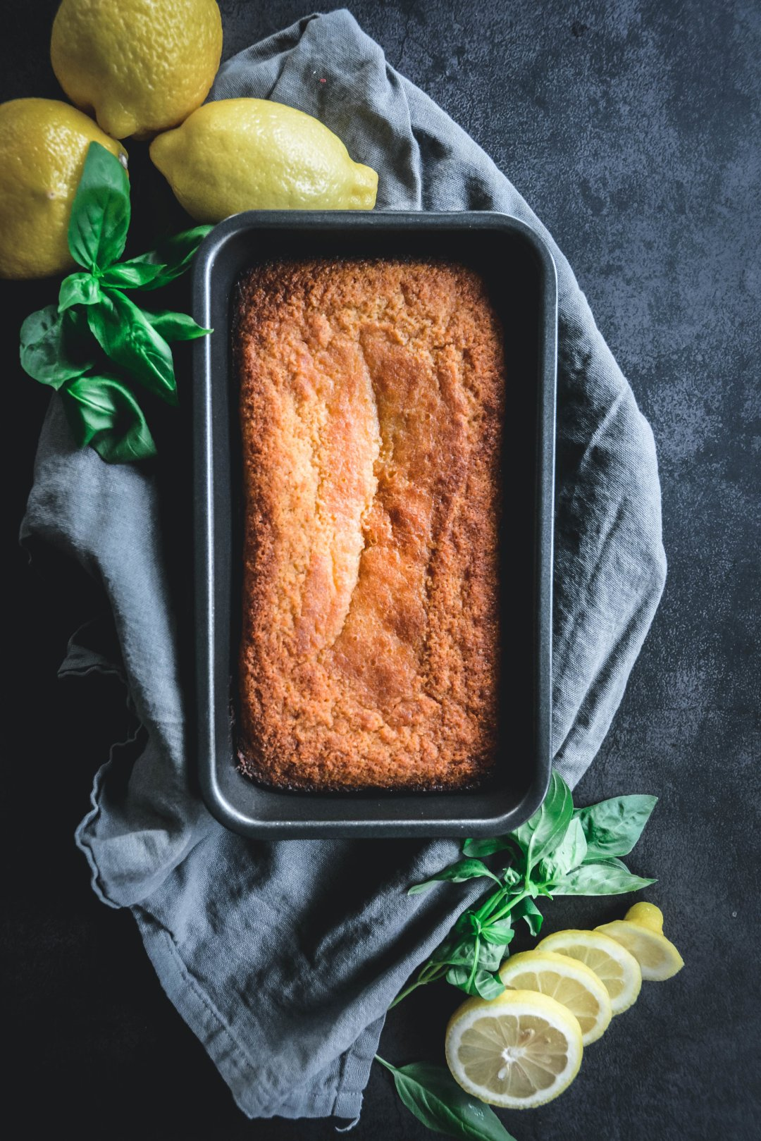 Loaf cake in pan on napkin with lemons