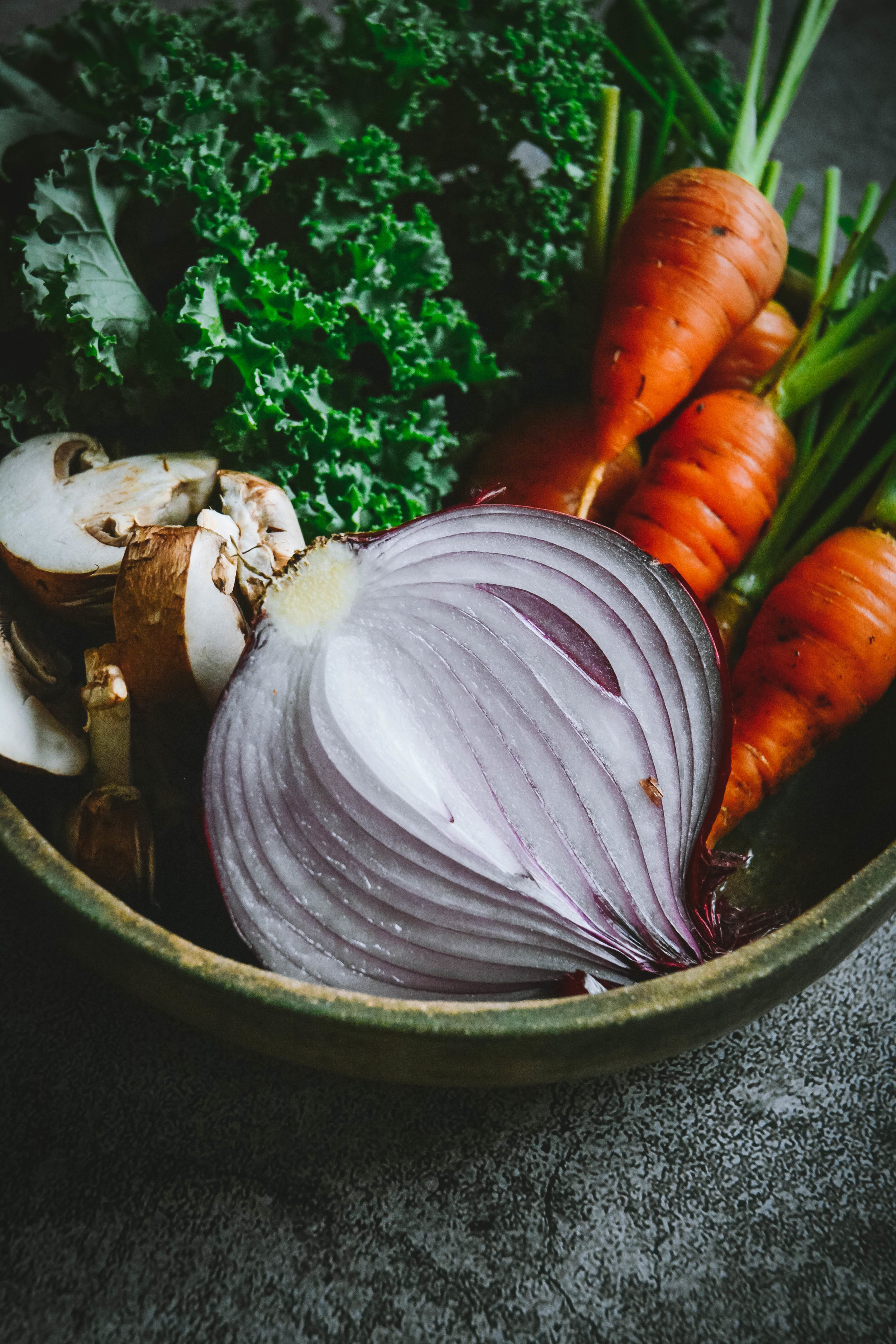Red onion, carrots and kale in bowl
