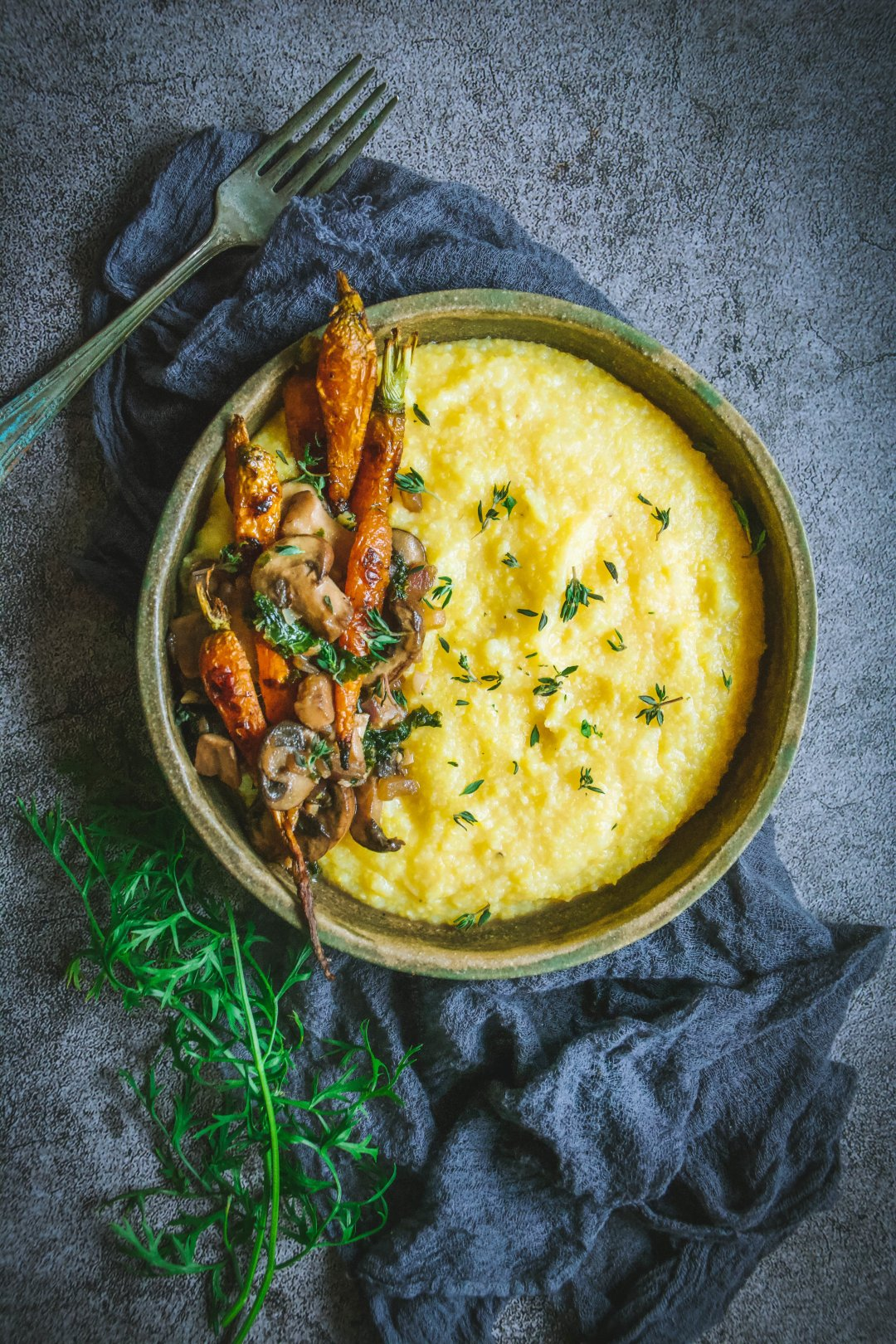 Polenta in bowl with mushrooms and roasted carrots