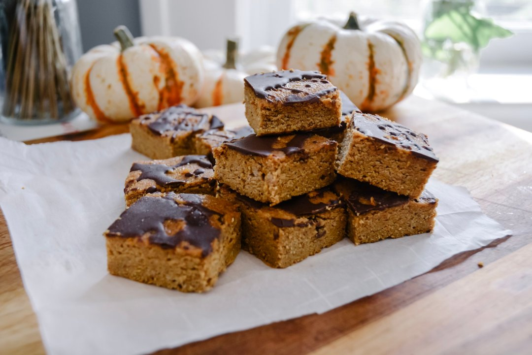 pumpkin bars on table with little pumpkins in the background