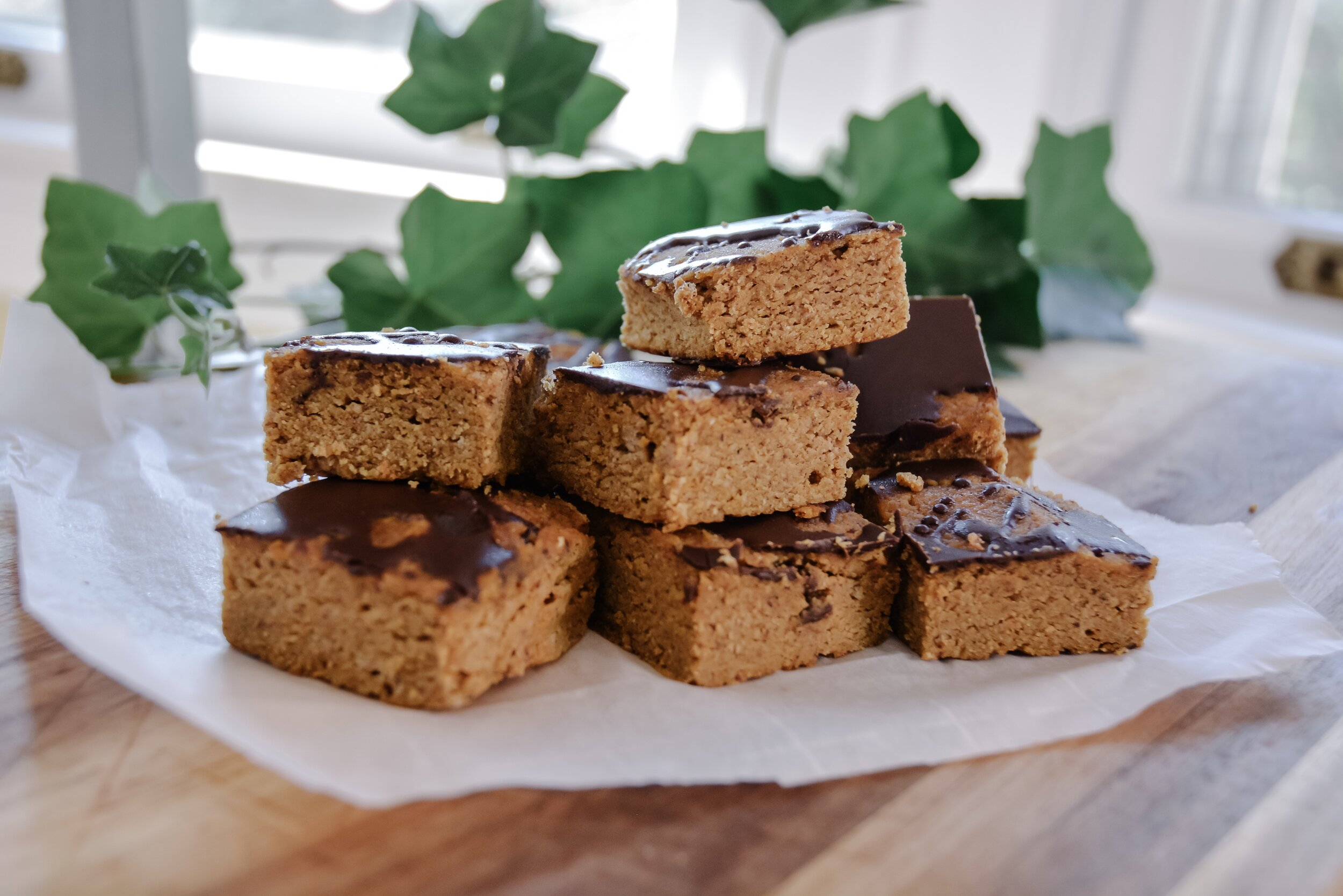 Paleo chocolate pumpkin bars on table with greens in the background