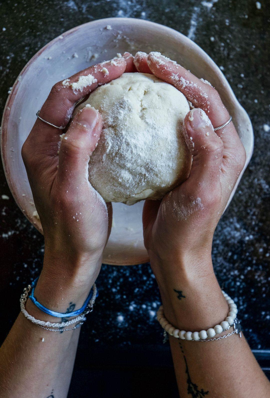Hands holding dough