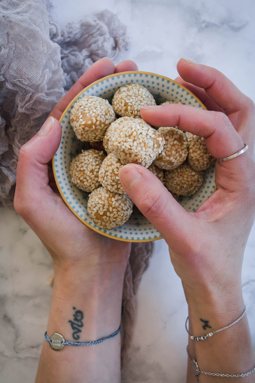 Hands holding bowl with peanut butter sesame balls