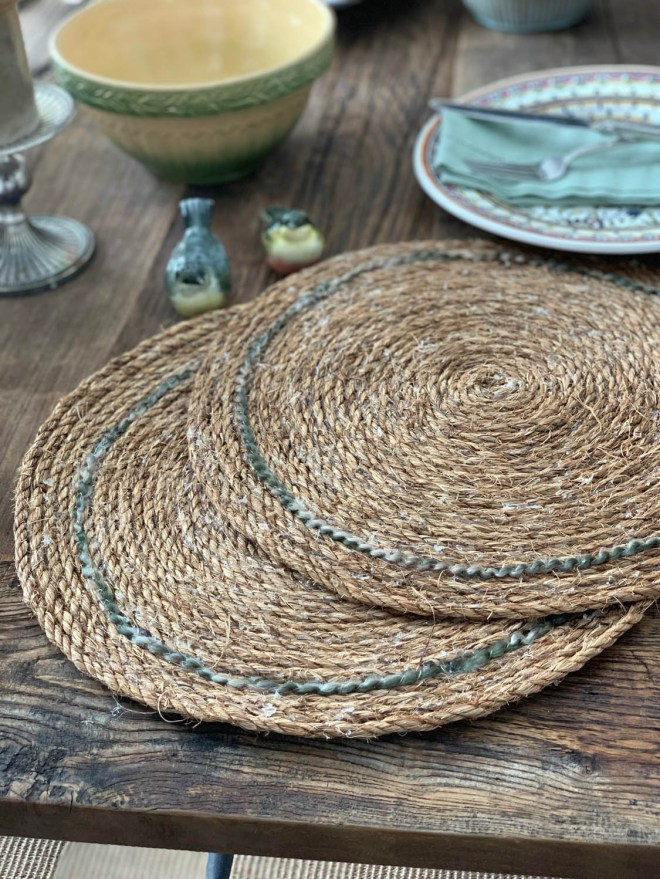 Pair of rustic handmade farmhouse rope placemats on a rustic barn wood dining table.
