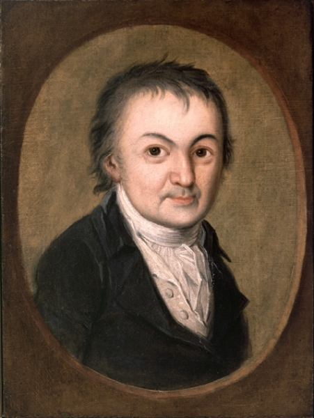 Image Description: oil painting of man in period clothing with tight collar. He is facing the viewer, with pursed lips and bright affect. He has straight, unkempt hair. He is wearing white shirt with collar and black jacket. The painting is framed as a photo, with oval brown frame.