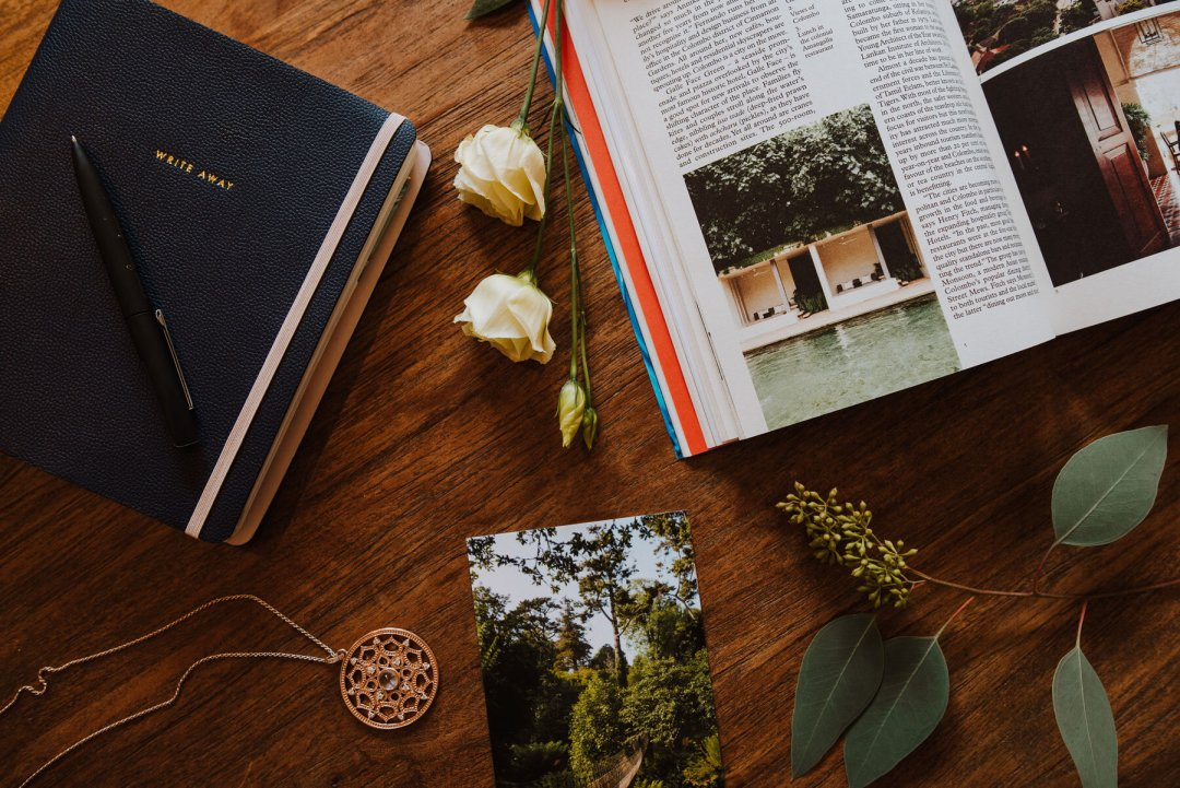 Flatlay of flowers, travel book and journal