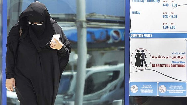 An Emirati woman passes by a dress code sign at a shopping mall in Dubai. An online campaign to get foreigns to dress respectfully has been gaining momentum.