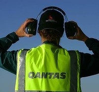 QANTAS STAFF PICTURE. BAGGAGE HANDLER QANTAS STAFF EMPLOYEE AVIATION FLYING LANDING TAKE OFF HOLIDAY TRAVEL AIRLINE COST CUTTING SAVINGS STOP AIRPORT TARMAC APRON NOISE SOUND CONTROL JET ENGINE SPECIALX 1234