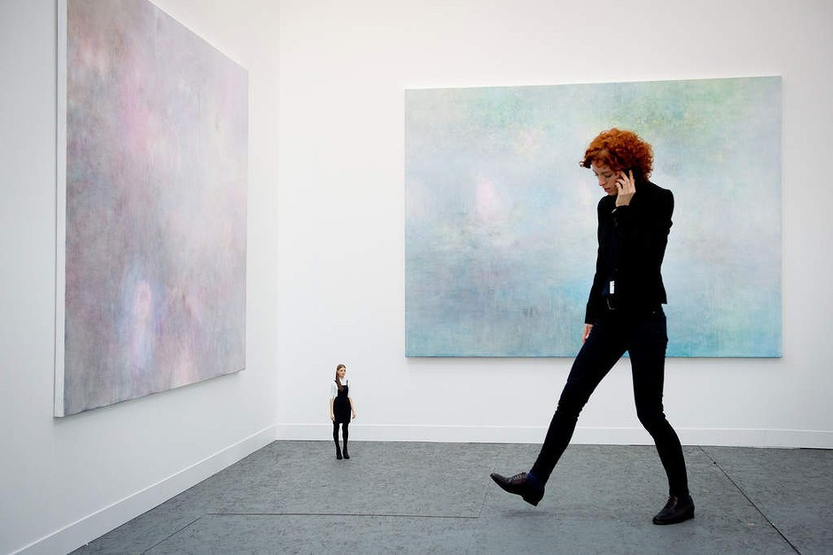 "A woman talks on her phone as she stands near works entitled ""Lounge Lover"" by British artist Dee Ferris (L), ""Nia"" by Japanese artist Tomoaki Suzuki (C) and ""Blue Milk"" by Dee Ferris (R)  at the Frieze London art fair in Regent's Park, north London, England"