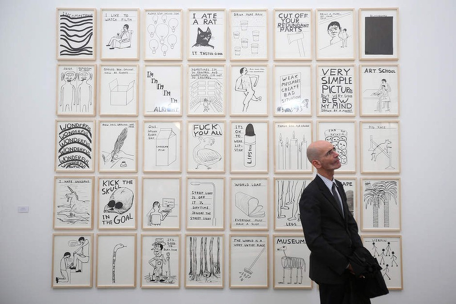 A man admires artworks by David Shrigley in the Frieze London art fair on October 16, 2013 in London, England.