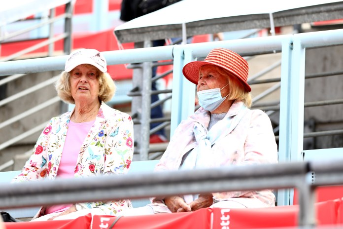 Two older women in spectator seats, one without mask, one worn improperly