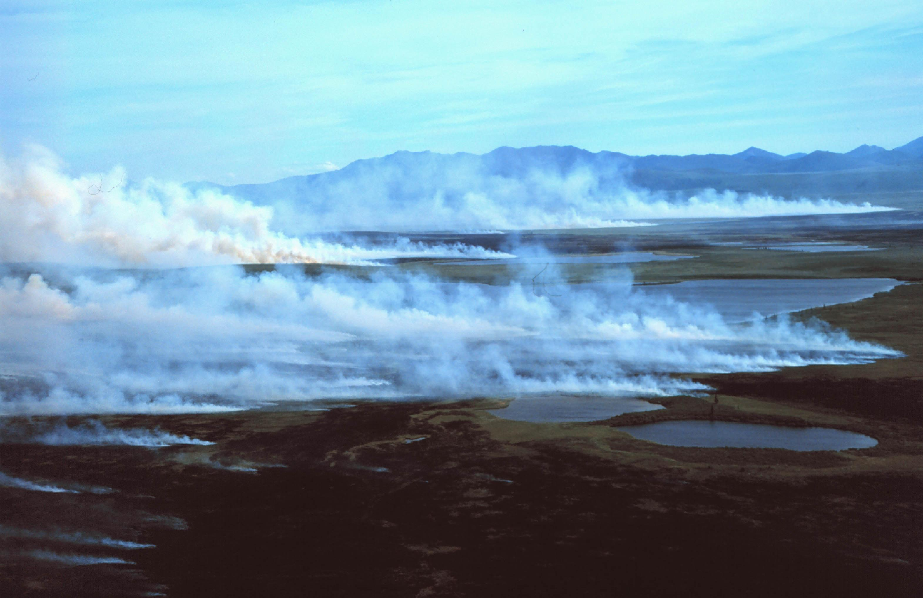 White smoke rises from the tundra with mountains in the background.