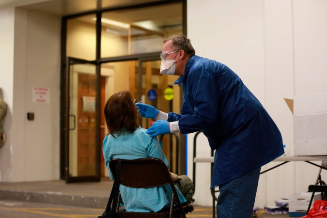 A doctor using a nasal swab to test a state senator of New Mexico.