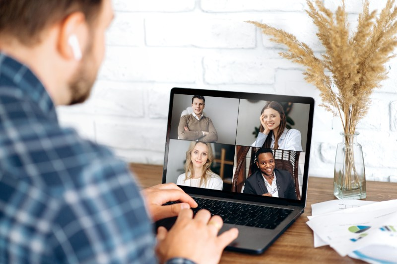 A man on his laptop in a video hookup with work colleagues.