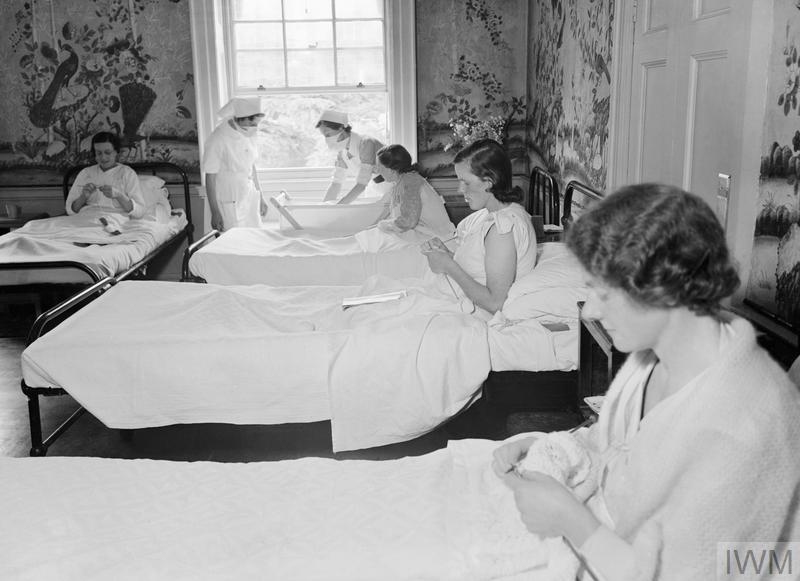 Historical image showing new mothers knitting in bed.