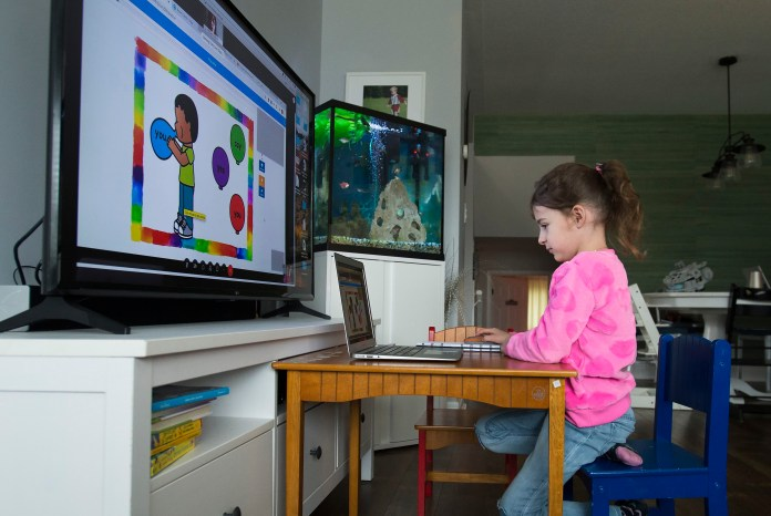A young girl in a pink sweatshirt sits in front of a laptop and a larger computer screen displaying lessons.