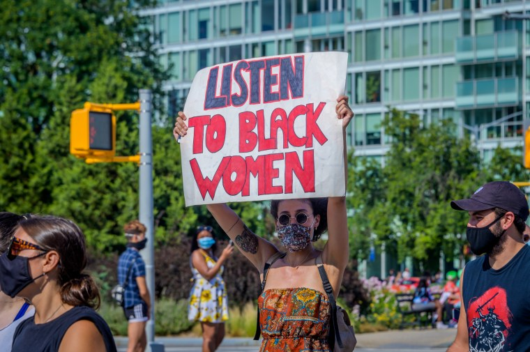 A participant holds a 'Listen to Black Women' sign at a protest in Fort Greene Park in Brooklyn, N.Y.