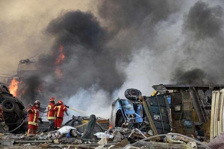Firefighters on the ground battle a blaze.