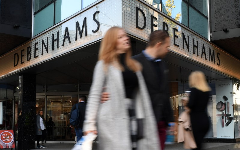 Shoppers walking past Debenhams