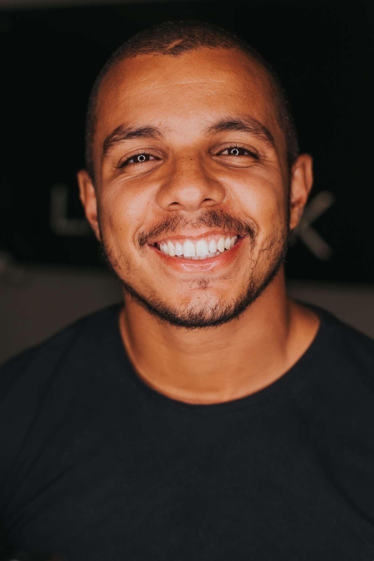 Un uomo con bei denti bianchi che sorride ampiamente.