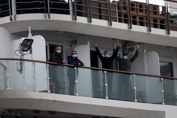 Four passengers wearing masks wave from a balcony aboard the Greg Mortimer cruise ship.
