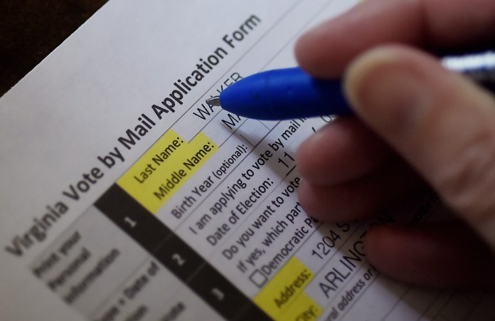 Voter filling out a Virginia ;vote-by-mail application.