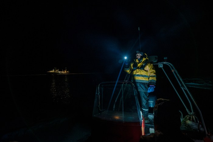 A man on a boat stands with a torch and looks into the polar night.