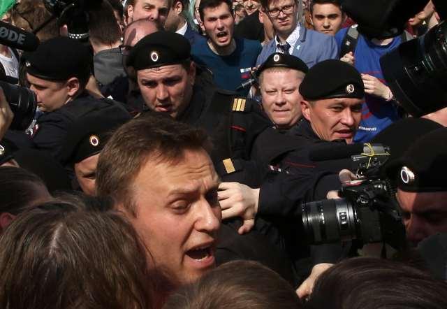 Riot police arresting opposition leader Navalny.