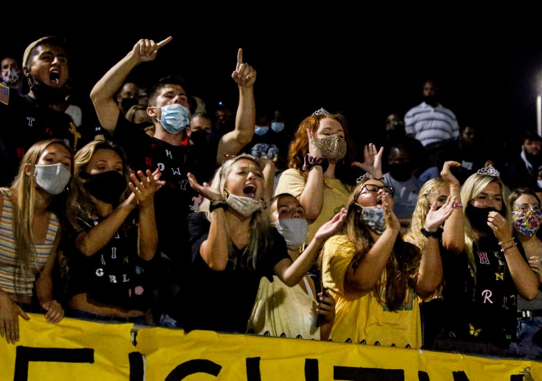 Students cheering at a high school football game.