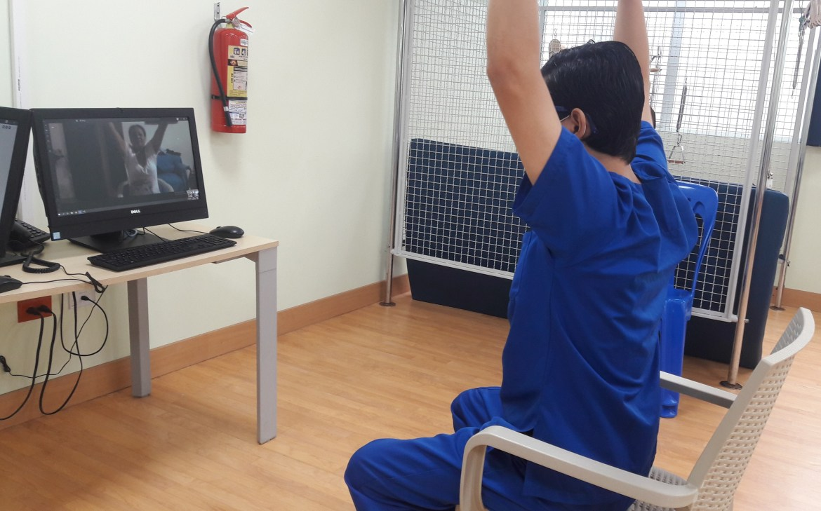 A medical professional guiding a patient through rehabilitation exercises over webcam.