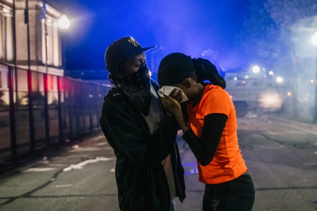 A man helping a woman during a street protest in Kenosha, Wisconsin.