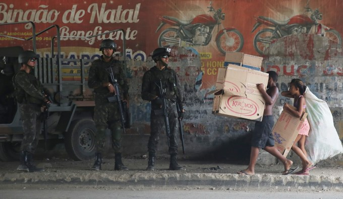 Heavily armed soldiers watch as a little boy and girl walk by carrying boxes