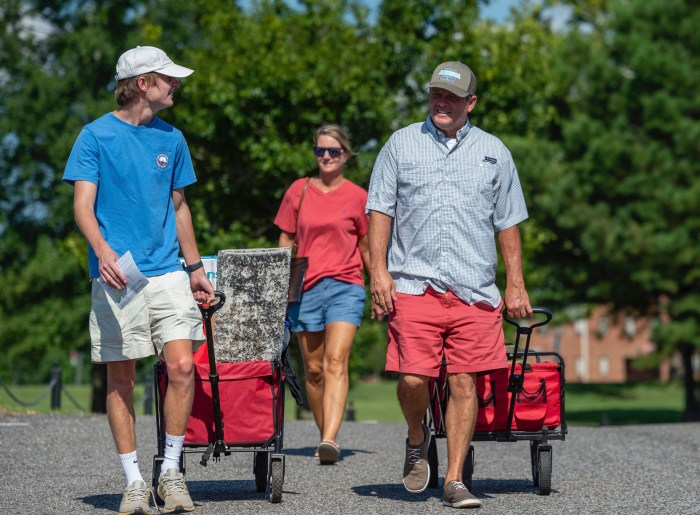 A freshman male walks with his parents toward his dorm.