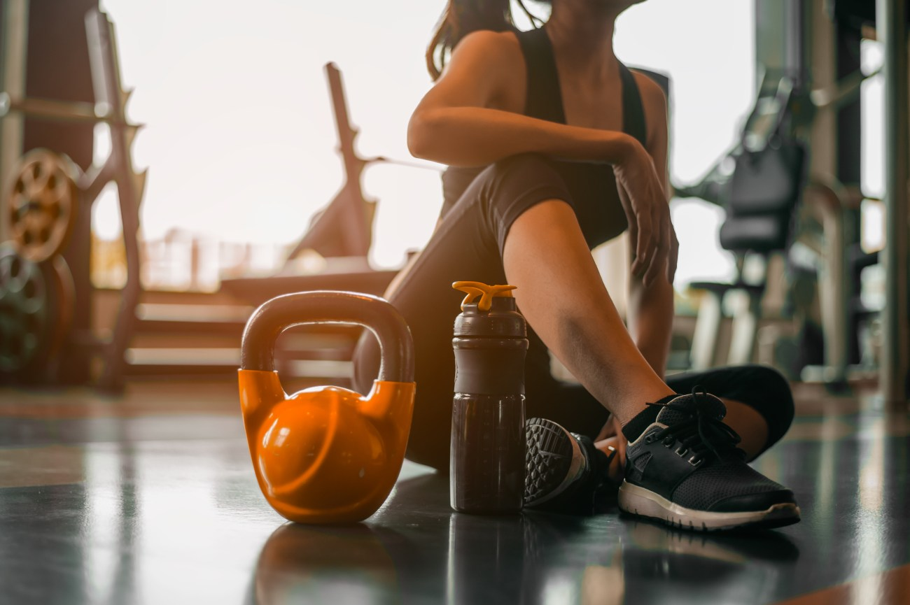 Woman sitting on the floor of gym with water bottle and kettlebell.